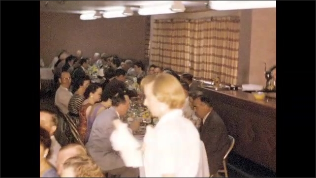 1940s: Large gathering of celebrants sit at long banquet tables in crowded function room as attendants bring them food and drink.