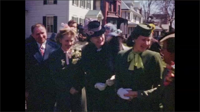 1950's: Churchgoers socialize on sidewalk after church service; red brick church exterior.