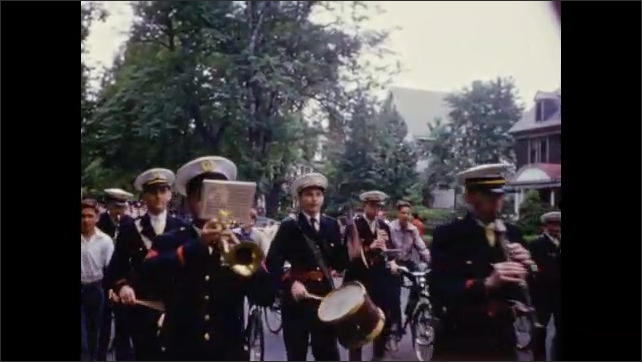 1950's: Platoon of policemen, marine marching band, soldiers in khaki march down residential street as crowds look on.