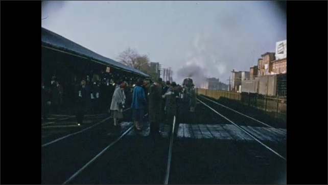 1950's: People stand along railroad tracks waiting for commuter train to arrive; train, belching smoke, pulls into station.