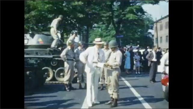1950's: Man in white suit wanders across plaza, seeking directions;  uniformed soldier points way; majorette marches down street.