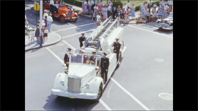 1950's: Fire department engines, ladder trucks, parade floats move down street.