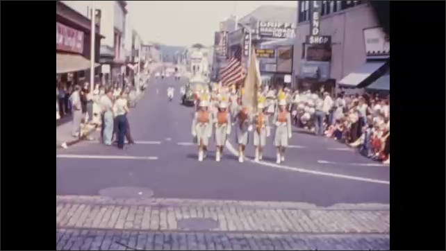 1950's: Figural locomotive float, statue of liberty float, girls marching band pass by in parade.