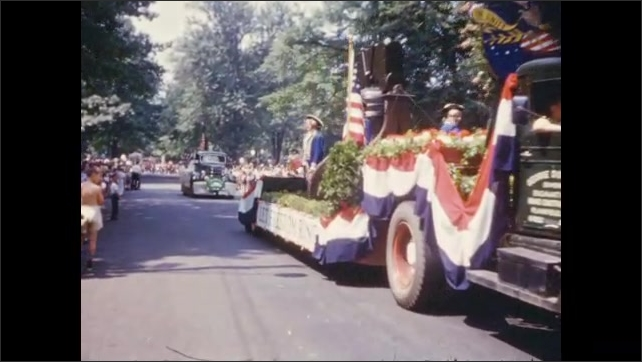 1950's: Beauty queens ride car bumpers in parade; Liberty Bell float passes by.