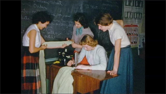 1950's: Female high school students work at sewing machine.