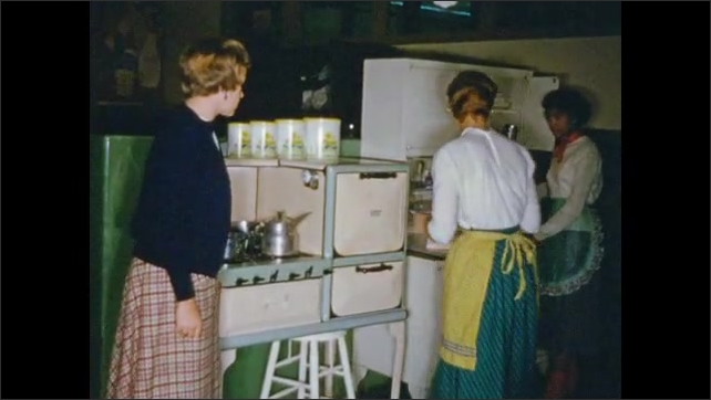 1950's: Female high school students work at stove in home economics class.
