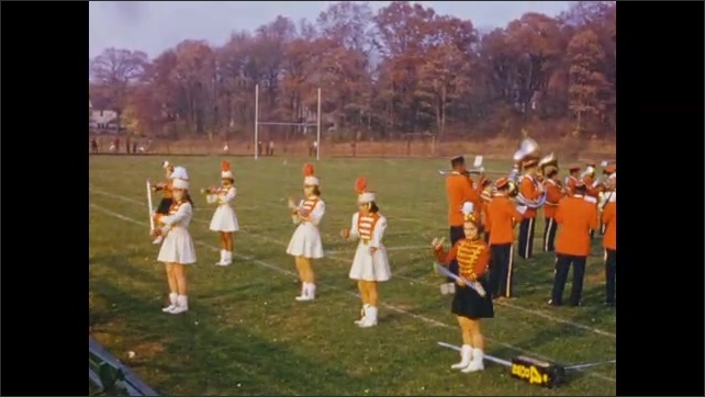 1950's: Marching band with majorettes and mascot perform routine on football field.