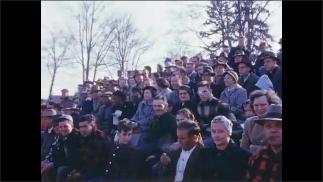 1950's: Large crowd of spectators sit in football grandstand; marching band takes seats.