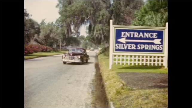 "1940s: Silver Springs roadside sign; man waves from passing automobile; homemade intertitle reads ""A morning stroll through the park."""