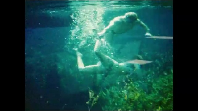 1940s: Man and woman dive from swimming platform, then viewed underwater as shot from Photo-Sub attraction; bodies kicking and swimming, bubbles swirling.