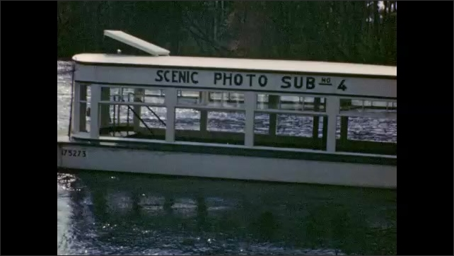 1940s: Passengers sit below-deck in underwater Photo-Sub tourist attraction; boat crosses inlet of water.