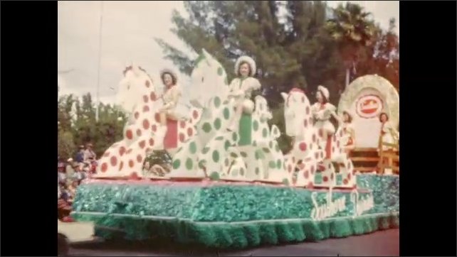 1940s: Parade of colorful floats with costumed beauty queens, majorettes and marching band.