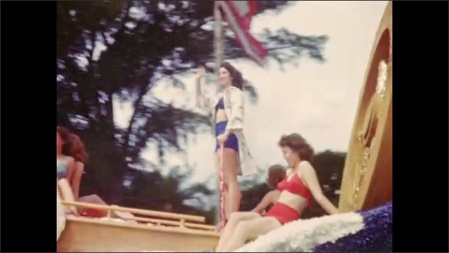 1940s: Parade of colorful floats with costumed beauty queens; Miss Coca-Cola waves to spectators.
