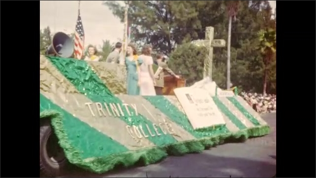 """1940s: Trinity College parade float moves down street, women in gowns waving. Humorous intertitle reads """". . . the bestest gals in Florida (hubba-hubba)"""""""