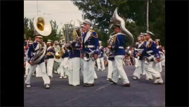 1940s: Parade of Navy bus, marching band, and colorful floats bearing costumed beauty queens waving to curbside crowds.