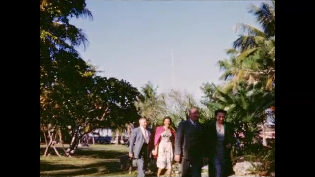 1940s: Two couples walk on lawn among palm trees