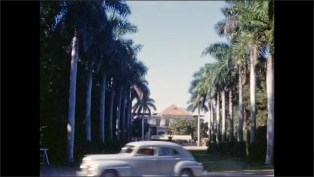 """1940s: Two women and man cross lawn; homemade intertitle reads """"Hialeah Race Track;"""" stately lawn lined with palm trees before mansion; visitors approach race track."""