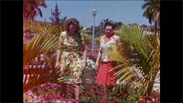 """1940s: Two women crouch amid lush flowers, walk  away; homemade intertitle reads """"Two petunias between petunias."""""""