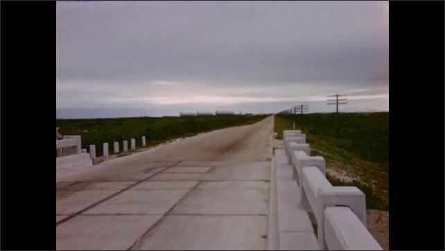 1940s: High-speed view of Seven Mile Bridge highway through auto windshield.