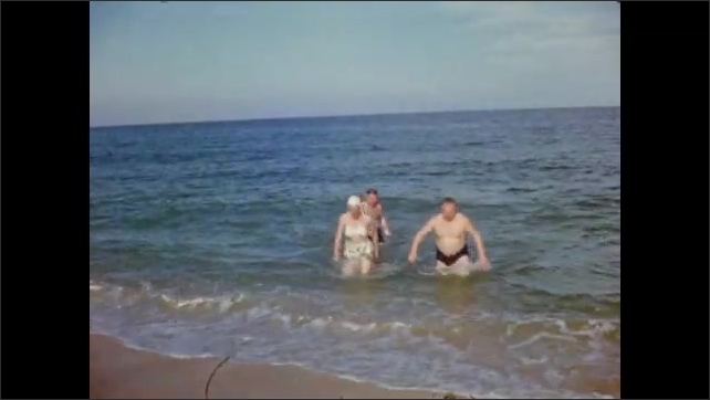 1940s: Three people, chest-deep in ocean, wave at viewer and wade to shore.