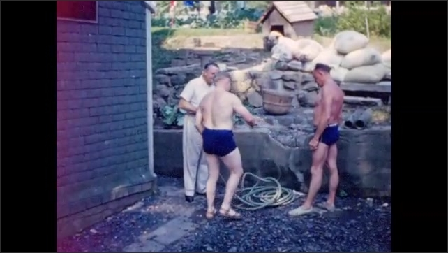 1940s: Two men in swimming trunks attach garden hose to spigot, wash large car.