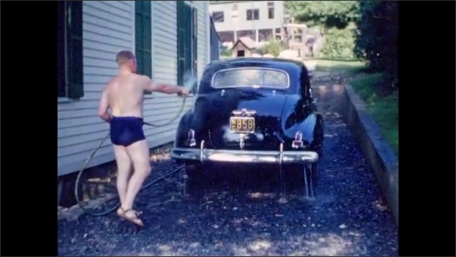 1940s: Man in swimming trunks washes car with garden hose; second man watches.