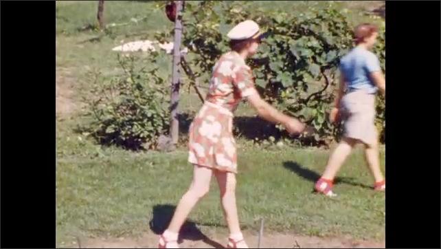 1940s: Two women play horseshoes; man takes careful aim, pitches horseshoe.