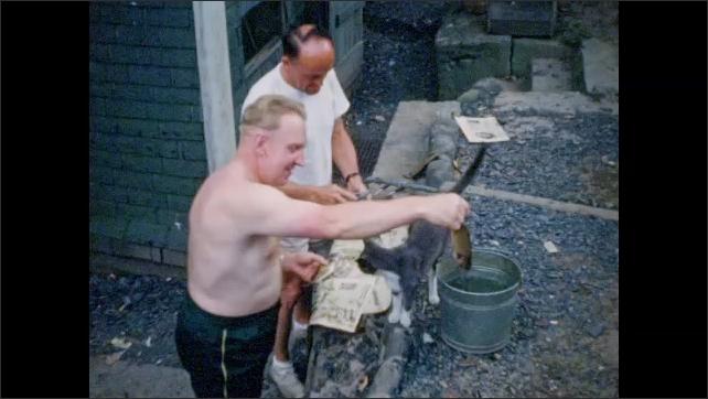 1940s: Men clean fresh fish on newspaper in yard as cat looks on.