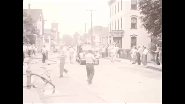 1940s: Man uncaps fire hydrant with wrench; hoses carry water to fire; fire truck backs down street while crowd looks on; smoke pours from burning building.