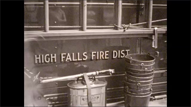 1940s: Man uses hose to douse fire on burning building; fire trucks, hoses, equipment on street; people milling about looking at spectacle.