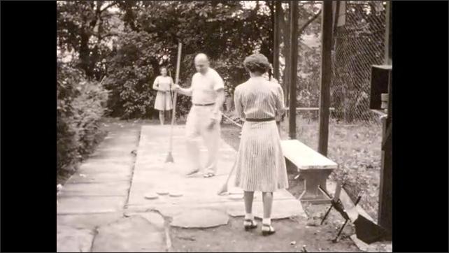 1940s: Two couples play shuffleboard; discs slide along concrete.