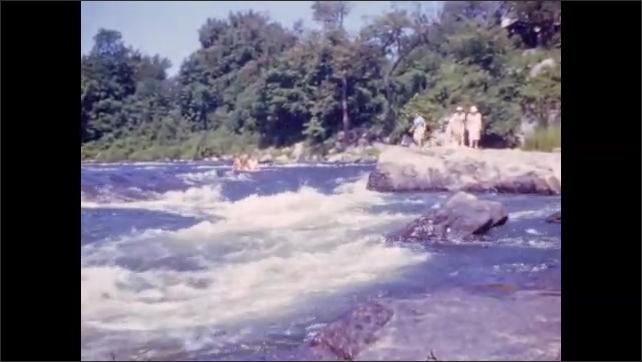 1940s: Water cascades down river; people walk on rocks at riverside.