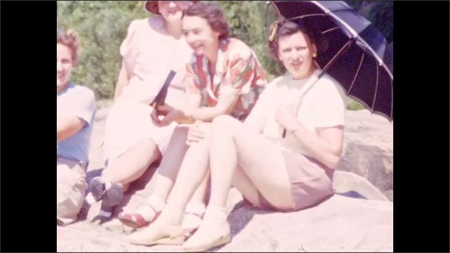 1940s: People sun themselves on rocks by river; women converse at river's edge; men wade in water.
