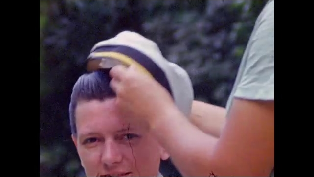 1940s: Man and woman make show of paying money to friends on lawn for barbering; woman fits commodore's hat on woman's head; man packs bag of supplies.