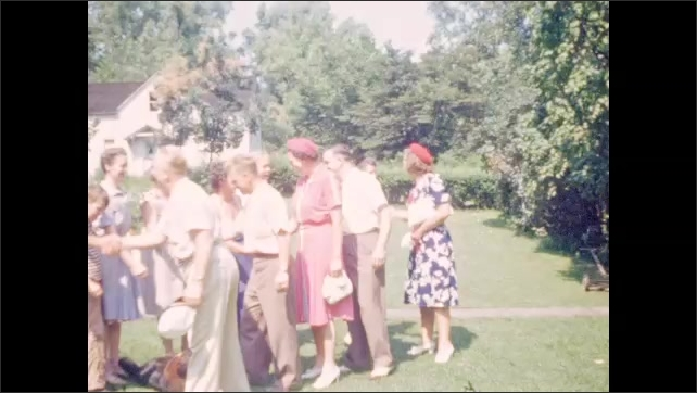1940s: Gathering of people shake hands on lawn prior to departure.