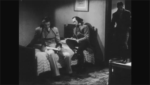1940s: man smokes pipe, sits in chair and talks to boy with striped coat, vest and cravat by fireplace in living room. men sit on bed and read books as student enters door, picks up book and chats.