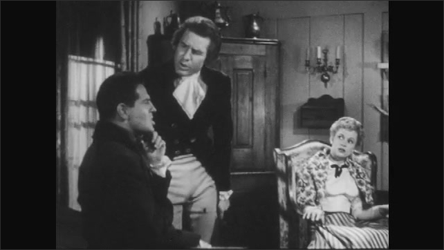 1940s: man sits in chair, listens and rubs chin while guy stands nearby and talks as woman leans forward and replies in living room with windows and a corner cabinet with copper pots.