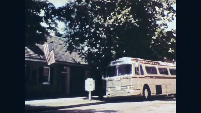 1960s: UNITED STATES: bus arrives in Fredericksburg. Bus pulls up by building.