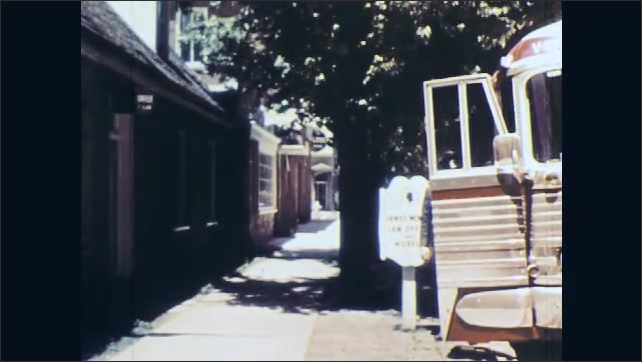 1960s: UNITED STATES: Door of bus opens. Ladies get off bus. Couple get off bus