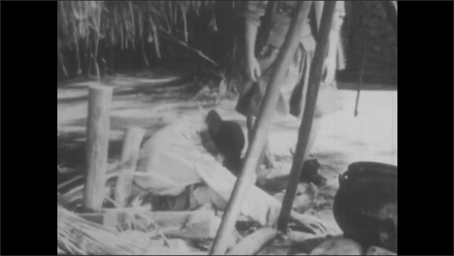 1950s: VIRGINIA, UNITED STATES: man talks to sick man in street. Man on ground in colony. Fishing nets broken.