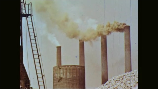 1960s: Molten liquid steel in furnace in factory. Block of molten steel is dropped from furnace. Smoke rises from smoke stacks of factory. Large turbines in factory. Electricity.