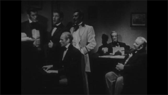 1940s: Men sitting at desk. Men singing at piano in office. Close up of sheet music.
