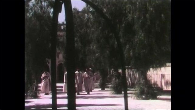 1950s: Priests in robes walk grounds of monastery.