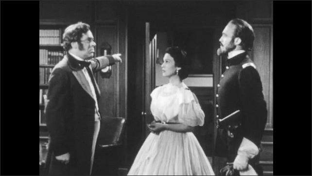 1950s: Men and woman talking in office, man points to door. Men and woman talk by door.
