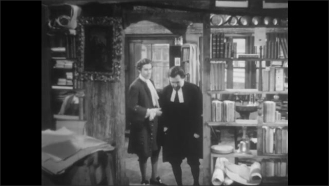 1950s: UNITED STATES: men talk in bookshop. Man takes cloak from visitor.