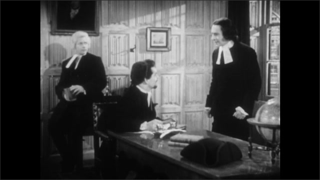 1950s: UNITED STATES: reverends talk in study. Man listens to reverend. Man sits at desk.
