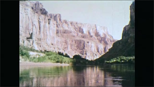 1960s: River calmly flowing. River at basin of Grand Canyon. In the water at base of Grand Canyon.