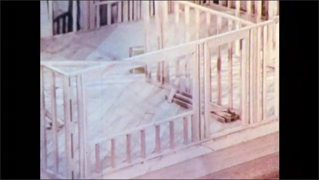 1960s: Men stand around model of frame of house. Men build frame of house.
