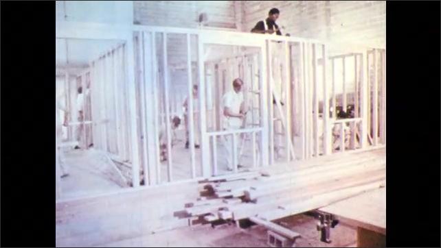 1960s: Men build frame of house.