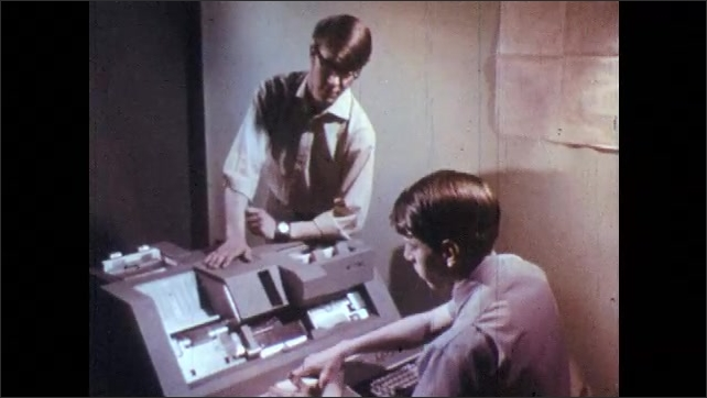 1960s: Punch cards travel through a machine. Man hands stack of punch cards to another man.